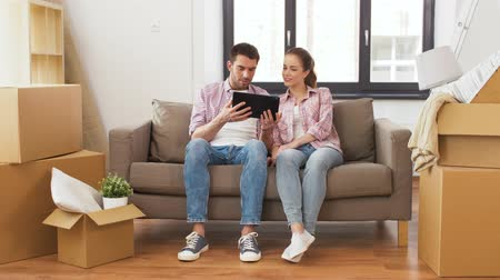 szállás : happy couple with tablet pc computer at new home