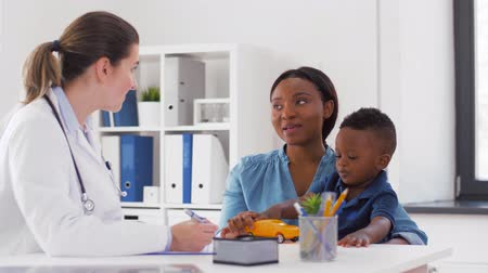 paediatrician : happy mother with baby son and doctor at clinic