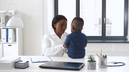 marker : doctor or pediatrician with baby patient at clinic Stock Footage