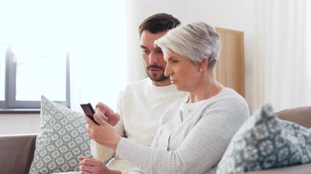parentes : old mother and adult son with smartphone at home Stock Footage