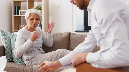 psychotherapist : psychologist giving glass of water to senior woman