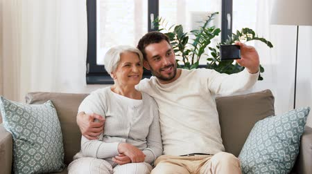 родственники : senior mother with adult son taking selfie at home