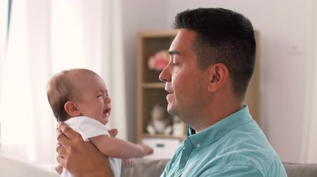 soothing : middle aged father with baby daughter at home