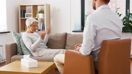 psychotherapist : senior woman patient talking to man psychologist