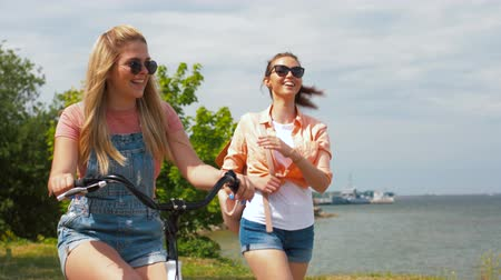 rögzített : teenage girls or friends with bicycle in summer Stock mozgókép