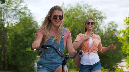fixní : teenage girls or friends with bicycle in summer Dostupné videozáznamy