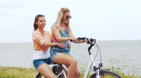 rögzített : teenage girls or friends riding bicycle in summer