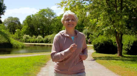amadurecer : senior woman running along summer park Stock Footage