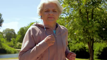 amadurecer : senior woman with earphones running in summer park Stock Footage