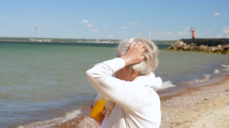słoma : senior woman drinking shake on summer beach Wideo