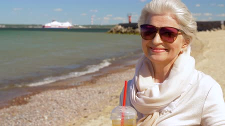 baltık denizi : senior woman drinking shake on summer beach Stok Video