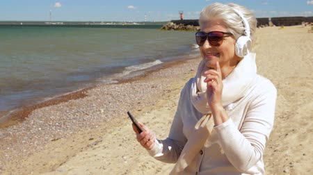 Észtország : old woman in headphones with smartphone on beach