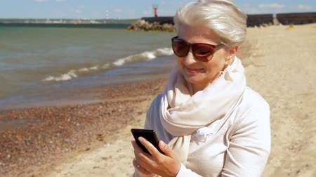 estonya : senior woman using smartphone on summer beach
