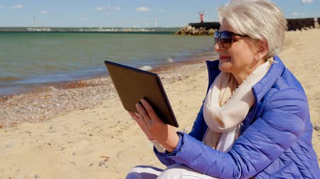 baltské moře : senior woman with tablet computer on beach