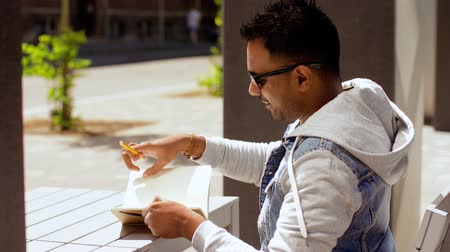 memo : man with notebook and coffee at street cafe Stock Footage