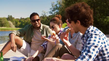 limonada : friends having picnic on pier at lake or river