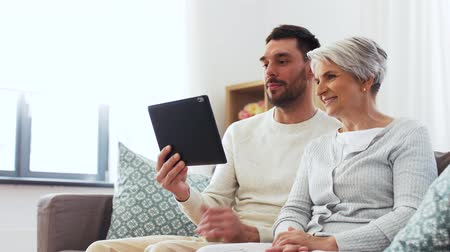ouder : old mother and adult son with tablet pc at home