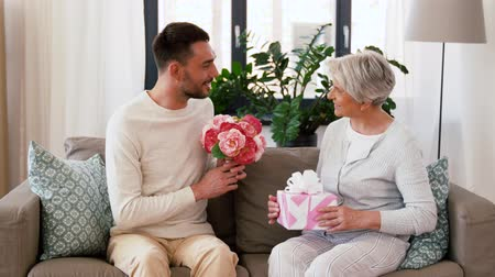 parentes : son giving present and flowers to senior mother