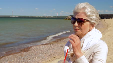 Észtország : senior woman drinking shake on summer beach Stock mozgókép