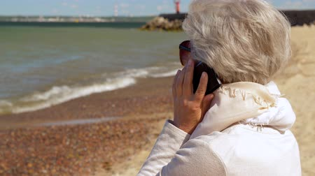 estonya : senior woman calling on smartphone on summer beach