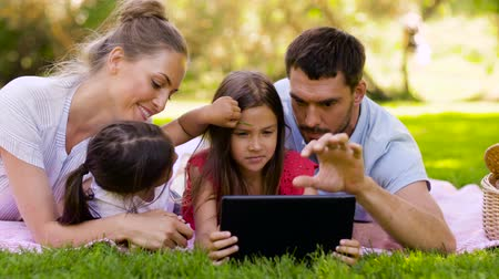 pre hispanic : family with tablet pc on picnic in summer park