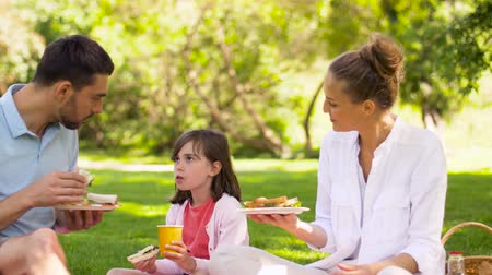 cesta de picnic : family eating sandwiches on picnic at summer park