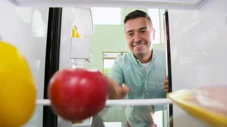 кусаться : man taking apple from fridge at home kitchen
