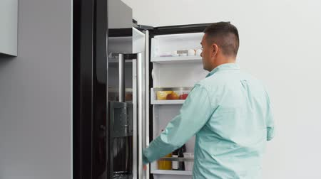 chladič : man taking banana from fridge at home kitchen