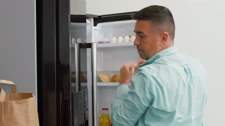chladič : man putting new purchased food to home fridge Dostupné videozáznamy