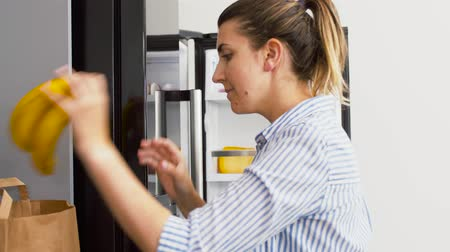 frig : woman putting new purchased food to home fridge Stock Footage