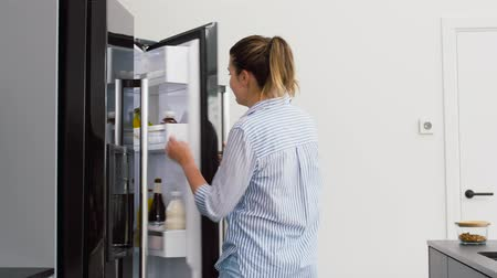 кулер : woman taking apple from fridge at home kitchen