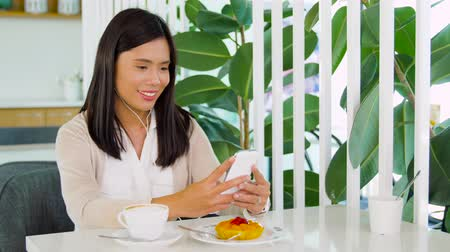 playlist : asian woman with smartphone and earphones at cafe Stock Footage