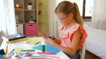 marker : girl cutting color paper with scissors at home