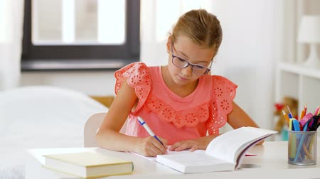school children : student girl with book writing to notebook at home Stock Footage