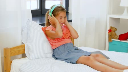 playlist : girl in headphones listening to music on tablet pc Stock Footage