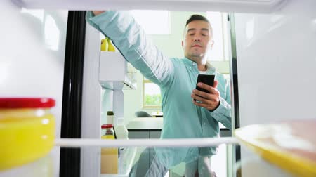 chladič : man with smartphone making list of food in fridge