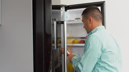closing : man making list of necessary food at home fridge