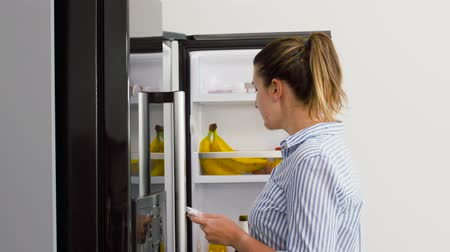 frig : woman making list of necessary food at home fridge