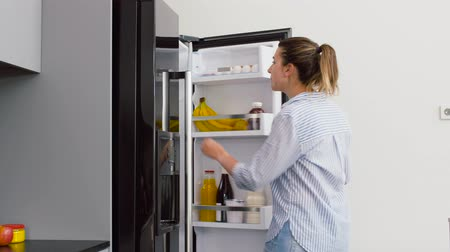 frig : woman taking banana from fridge at home kitchen Stock Footage