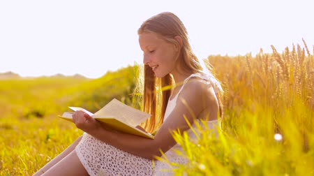 árpa : smiling young girl reading book on cereal field