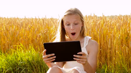 pré adolescente : smiling with tablet computer on cereal field