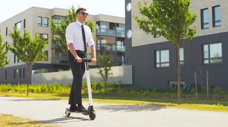 beyaz yakalı işçi : young businessman riding electric scooter outdoors