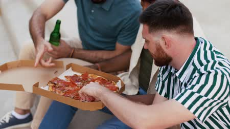 foods : male friends eating pizza with beer on rooftop Stock Footage