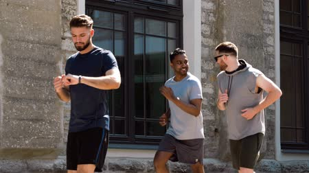 warming up : young men or male friends running outdoors Stock Footage
