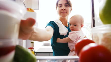 yoghurt : mother with baby taking food from fridge at home