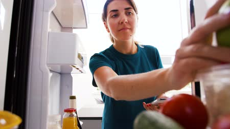 revisione : woman making list of food on smartphone at fridge