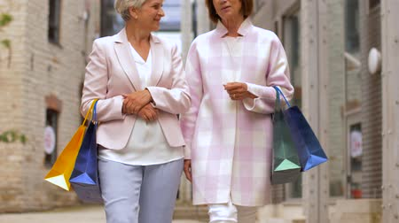 consumerism : senior women with shopping bags walking in city Stock Footage