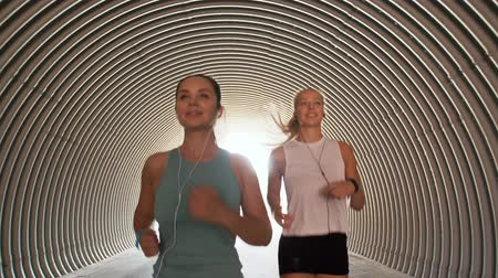 fitness tracker : women or female friends with earphones running