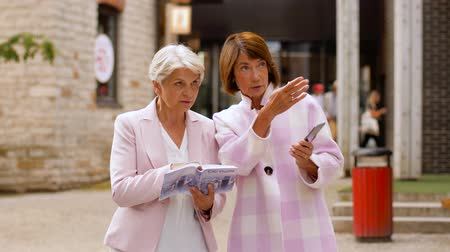 estonia : senior women with city guide and smartphone