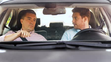 rijles : car driving school instructor teaching man driver